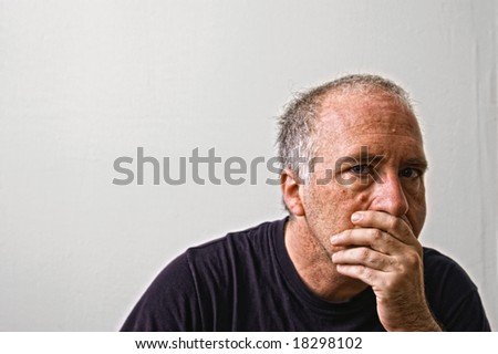 beautifully detailed real portrait of haggared looking adult white man staring intensely at the viewer with hand over mouth and black t-shirt - stock photo