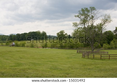 Beautifully green horse pasture with curving fence under cloudy skies.