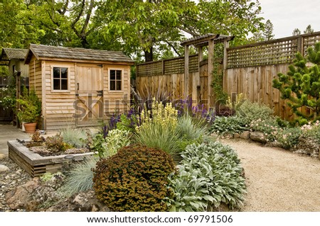 beautifully landscaped backyard with small wooden shed, fence and pathway - stock photo