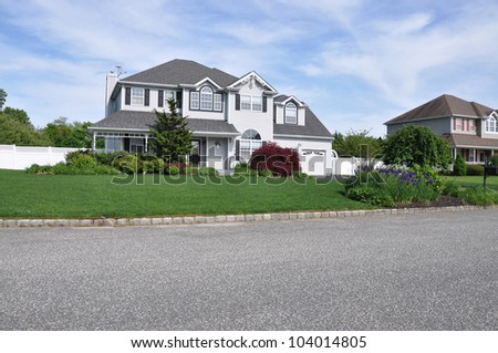 Beautifully Landscaped Two Story Suburban Home with blooming purple iris flowers curbside - stock photo
