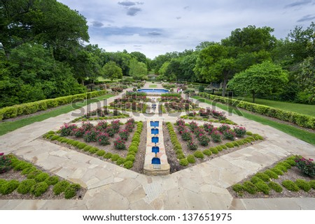 Beautifully landscaped urban rose garden on a cloudy spring day in Texas - stock photo