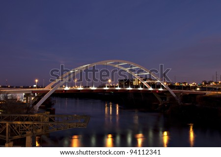 Beautifully lit arched bridge with colorful reflections
