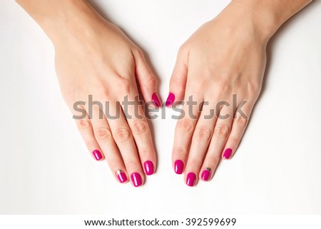 Beautifully manicured fingernails with fuchsia nail polish on a white background.