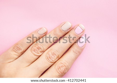 Beautifully manicured fingernails with natural nail polish on a light pink background.