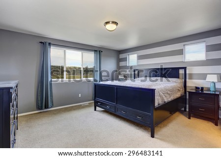 Beautifully modern bedroom with gray stripped walls, and large bed. - stock photo