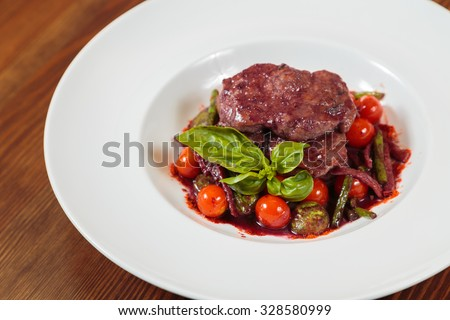 Beautifully presented dish of meat and vegetables. Tasty grilled meat sauce. Appetizing and healthy food. Photo for culinary magazines, websites and backgrounds.  - stock photo