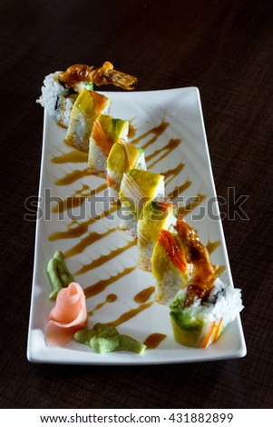 beautifully presented tempura shrimp roll with a sweet sauce and avocado - stock photo
