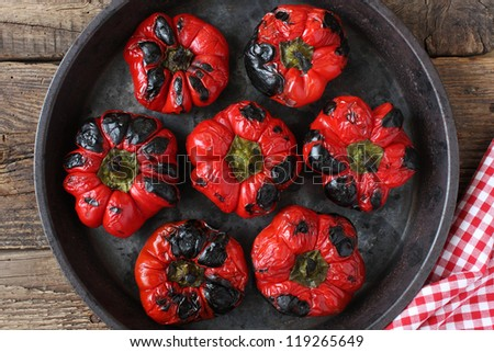 Beautifully roasted red bell peppers in a round pan on a wooden board next to a kitchen cloth. Rustic take from above. - stock photo