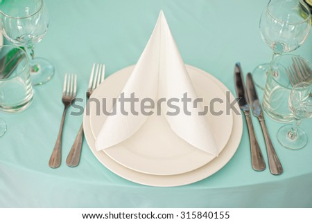 Beautifully served table in a restaurant / Beautiful holiday table setting in white and blue color  - stock photo