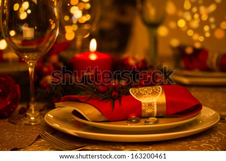 Beautifully set table in red and gold for Christmas Eve - stock photo