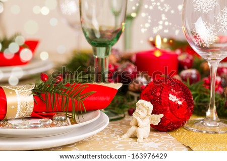 Beautifully set table in red and gold for Christmas Eve