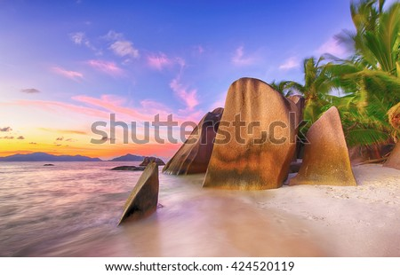 Beautifully shaped granite boulders and a dramatic sunset  at Anse Source d'Argent beach, La Digue island, Seychelles - stock photo