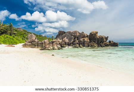 Beautifully shaped granite boulders in the turquoise sea  and a perfect white sand at Anse Coco, La Digue island, Seychelles. Panorama - stock photo