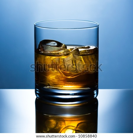 Beautifully shined glass from whiskey with ice is reflected in a glass table - stock photo