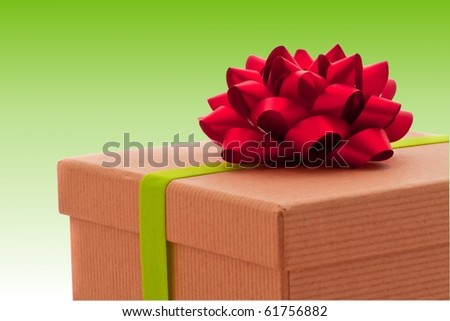 Beautifully wrapped present on green background, red bow - stock photo