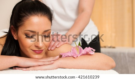 Beautifuly oung woman having a rejuvenating massage in a wellness studio - spa - stock photo
