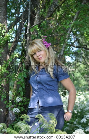 Beautigul blonde woman standing in the wood with violet flower