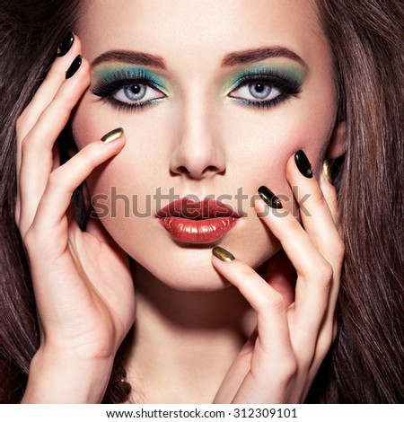 Beautiul woman with green make-up and creative color of nails - stock photo