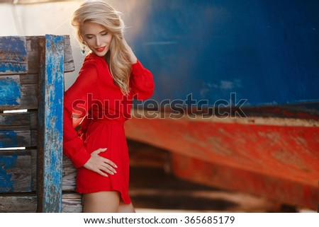 beautty fashion portrait of blonde woman with red lips. Portrait of the young beautiful smiling woman outdoors enjoying summer sun. Fashion woman in red drees with red lips. Young woman portrait.  - stock photo