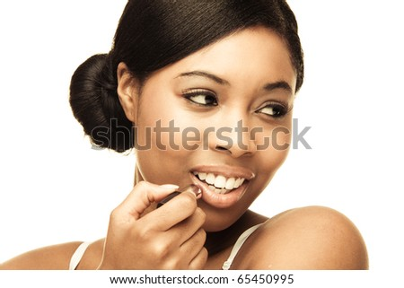 beauty african woman applying her make-up - stock photo
