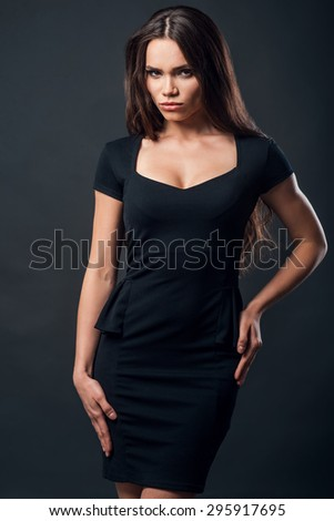 Beauty and confidence. Attractive young woman in black dress holding hand on hips and looking at camera while standing against black background - stock photo