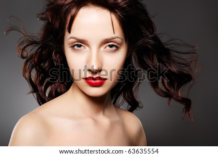 Beauty and fashion. Cosmetics and make-up. Portrait of luxury woman model with juicy red lips and long curly brown hair. - stock photo
