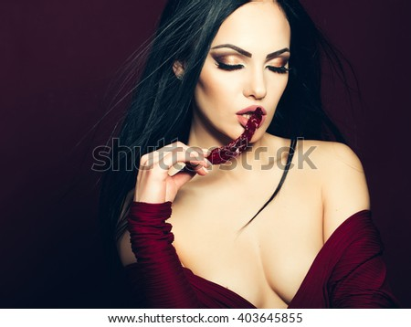 Beauty and fashion, food. Woman in dress with red pepper near mouth in studio