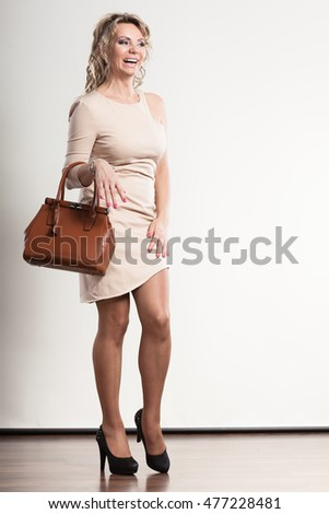 Beauty and fashion. Middle aged blonde stylish woman in full length wearing bright dress high heels shoes holds brown handbag, studio shot on gray