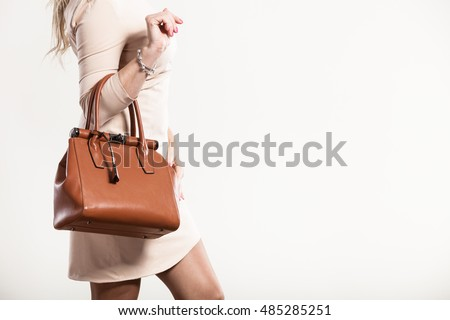 Beauty and fashion. Stylish fashionable woman wearing bright dress holding brown bag handbag, studio shot