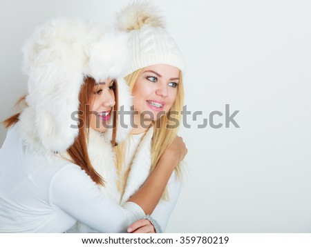 Beauty and fashion. Wintertime concept. Two attractive girls blonde and mixed race in winter clothing warm white cap hat. Studio shot.