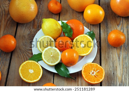 Beauty and health, food and drink, diet and nutrition concept. Citrus fruits (orange, lemon, tangerine) on a wooden table. Selective focus, top view - stock photo