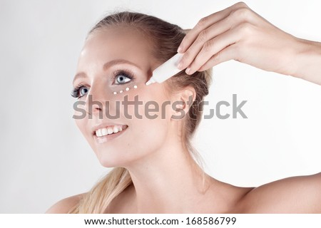 Beauty and healthcare, make-up & cosmetic. Skincare. Light close-up portrait of beautiful woman with daily cream on white background. - stock photo