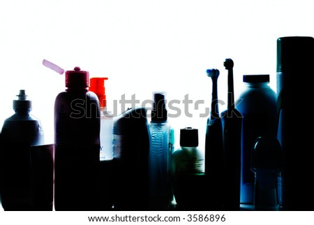 Beauty and hygiene products silouhetted on shelf of bathroom cabinet