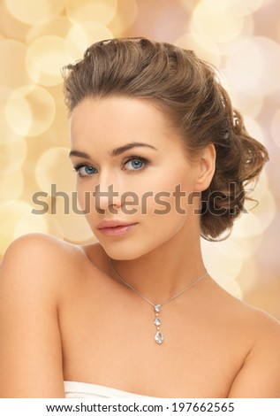 beauty and jewelry concept - woman wearing shiny diamond pendant - stock photo