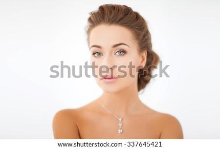 beauty and jewelry concept - woman wearing shiny diamond pendant - stock photo