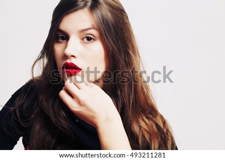 Beauty and Makeup concept. Beautiful fashion model woman with bright make-up. Trendy red lips. Long eyelashes. High fashion portrait with blank copy space alongside.