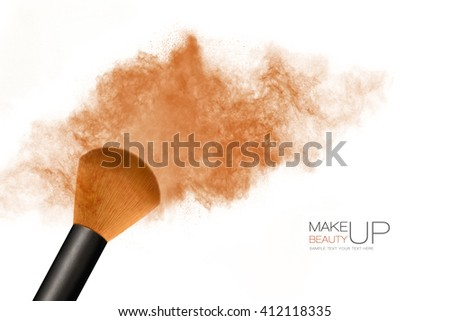 Beauty and Makeup concept. Cosmetics brush releasing a cloud of bronzing face powder explosion over a white background with copy space for text - stock photo