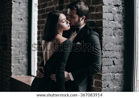 Beauty and passion. Beautiful young loving couple bonding to each other while both standing against brick wall indoors