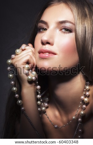 Beauty and pearl necklace on dark background - stock photo