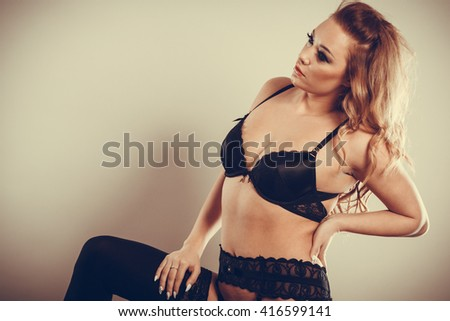 Beauty and sexiness of female body. Attractive seductive young woman in black lingerie. Portrait of sexy gorgeous and provocative girl. - stock photo