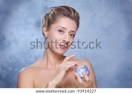 Beauty and skin care / Beautiful blond woman holding moisturizing face cream