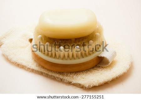 Beauty and skin care. Spa products bath accessories scrub brush soap and massage glove on wooden table. - stock photo