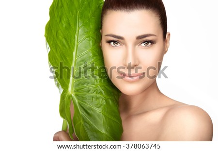 Beauty and skincare portrait. Beautiful spa girl with the large fresh green leaf of a tropical plant against her cheek as she looks at the camera with a gentle smile in a spa and wellness concept - stock photo