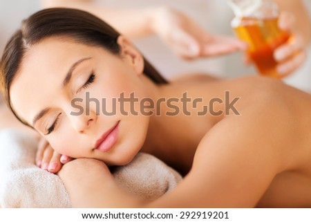 beauty and spa concept - beautiful woman in spa salon getting oil treatment - stock photo