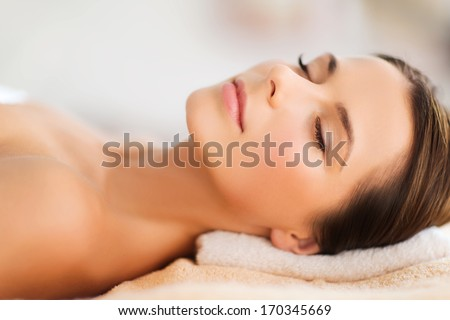 beauty and spa concept - beautiful woman in spa salon lying on the massage desk - stock photo