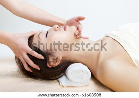 Beauty and Spa - Young Girl having a massage on her face - stock photo