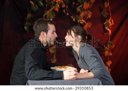 beauty and the tramp: young couple at the restaurant eating pasta