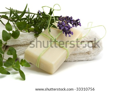 beauty and wellness concept - handmade herbal soap and towel with lavender, rosemary, thyme isolated on white