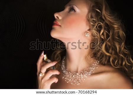 Beauty applying perfume on her neck - stock photo