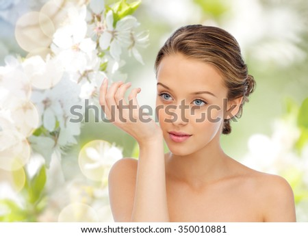 beauty, aroma, people and body care concept - young woman smelling perfume from wrist of her hand over green natural cherry blossom background - stock photo